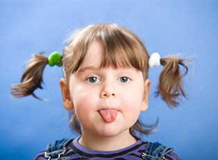 Little girl with weird pigtails sticks out her tongue