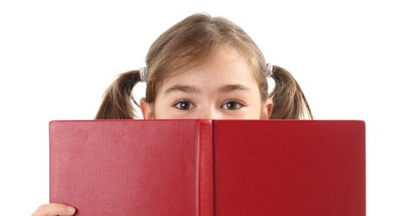 A young girl reads a red book
