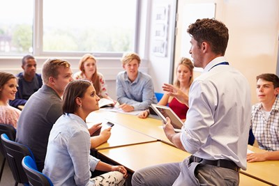teacher talking to students in classroom at community college