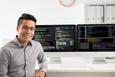 a man at his desk working a job as a software engineer on split screens with coding languages on them