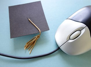 Graduation cap sitting next to a computer mouse after you obtain an electrical engineering degree