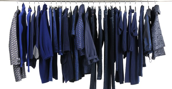 Blue articles of clothing hang in a closet