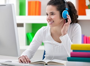 Girl wearing headphones smiles at her computer