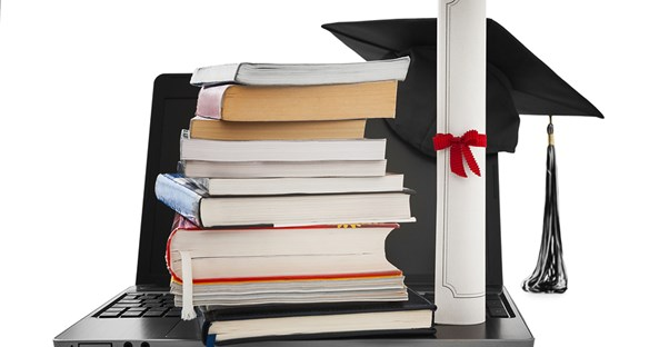 A degree sits on top of a laptop along with a stack of books