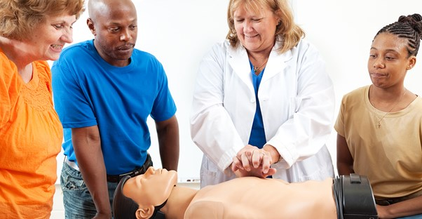 A group of aspiring EMTs practice on a dummy