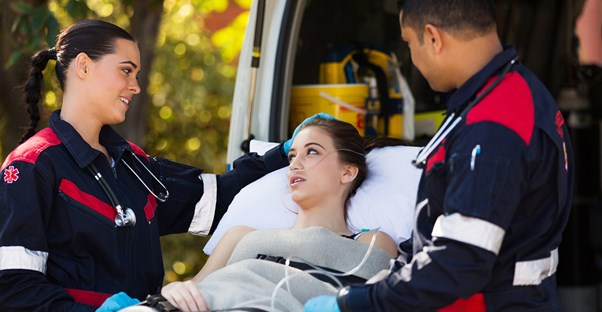 EMTs comfort a young girl on a stretcher