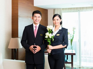 Hospitality managers bring flowers to a hotel room
