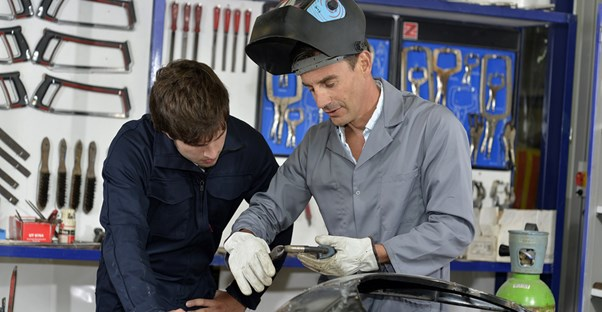 A teacher shows a welding student how to use welding tools