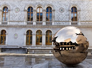 Giant metallic sphere shaped sculpture sits next to an old building
