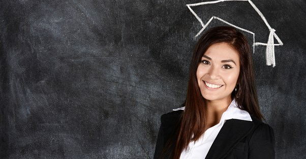 A girl poses under a drawing of a graduation cap on a blackboard