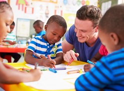 A preschool teacher colors with preschool students