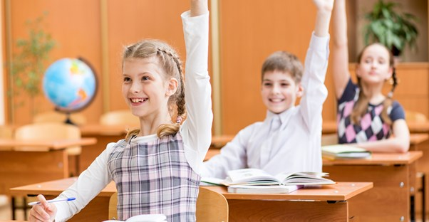 Students raise their hands during class