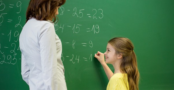 Teacher watches a young student write on the chalkboard