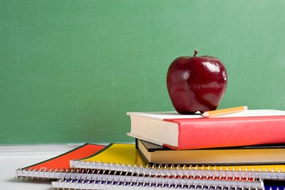 An apple sits on top of school books
