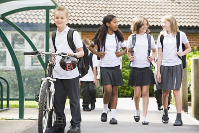 Young students walk home after school in their matching school uniforms