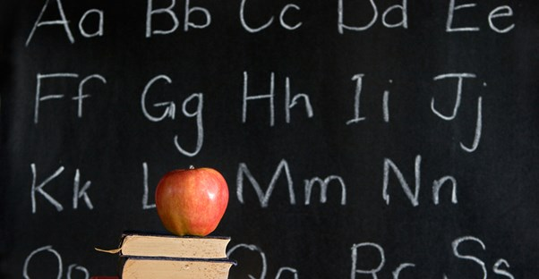 An apple on a stack of books on a desk in front of a chalkboard