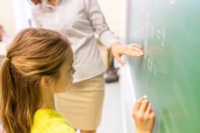 A student works out a math problem on the chalkboard