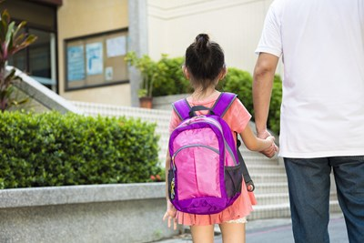 A parent walks their child to school
