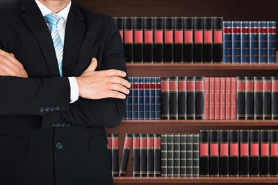 Man in a suit stands in front of a bookshelf
