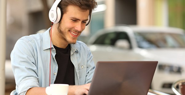 Man wearing headphones sitting at cafe on laptop computer