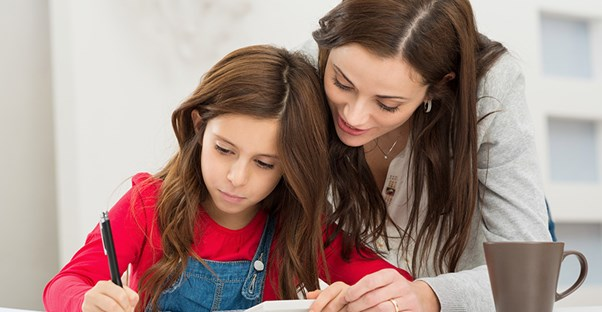 A mother helps her daughter with her math homework