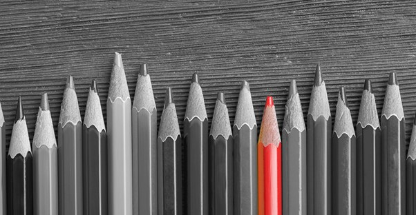 black and white photo of pencils lined up on a special education teacher's desk, with one pencil colored in red.
