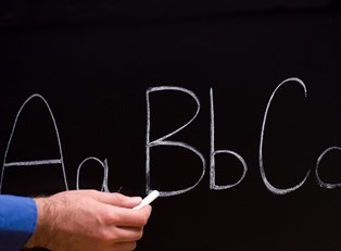 Teacher write ABCs on a chalkboard
