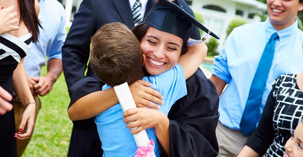 A happy graduate hugs a young boy
