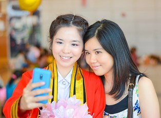 Two girls take a selfie on graduation day