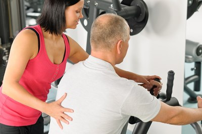 A personal trainer works with a client