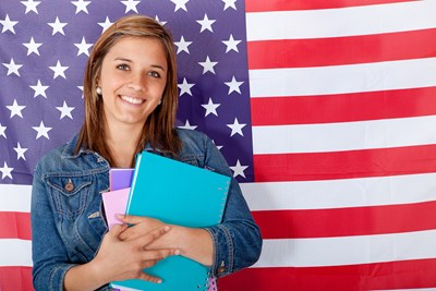 A young girl stands in front of an American flag