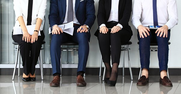 Young professionals sit and wait in a waiting room