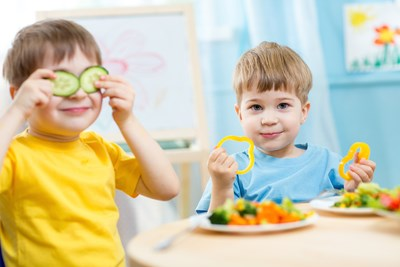 Young kids play with food in the cafeteria