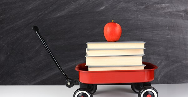 A wagon with books and an apple on top