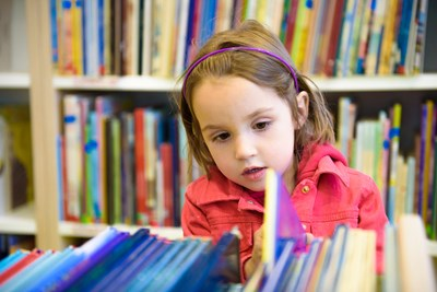 A young preschooler looks through books in the school library